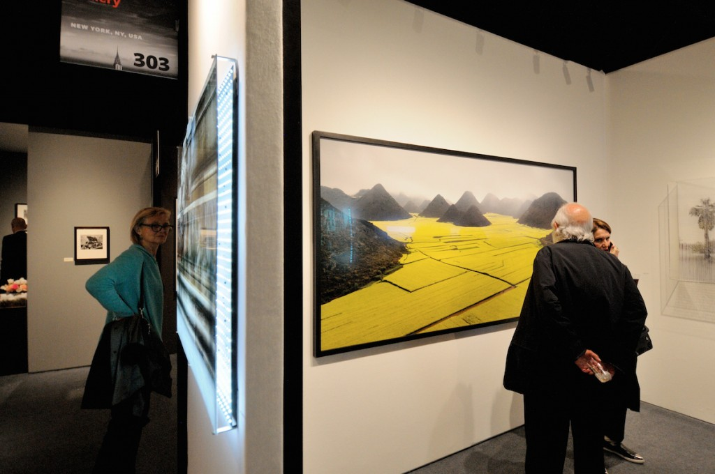 An unexpected link is formed between two art works featured by Bryce Wolkowitz Gallery:a reflection of a multimedia installation by San Francisco based artist Jim Campbell in a large format photograph by Edward Burtynsky of Canada. Burtynsky's striking photograph of the yellow canola fields in China's Yunnan province (right) was shot while working on his Water series but was released only recently. The latest Parisian-themed innovative piece by Jim Campbell (center) creatively integrates 1,200 LED lights, a photographic still and a video of the same image that is interpreted by an integrated computer to create the effect of flowing water. Jim Campbell is a graduate of Massachusetts Institute of Technology and holds nearly twenty patents in the field of video image processing.